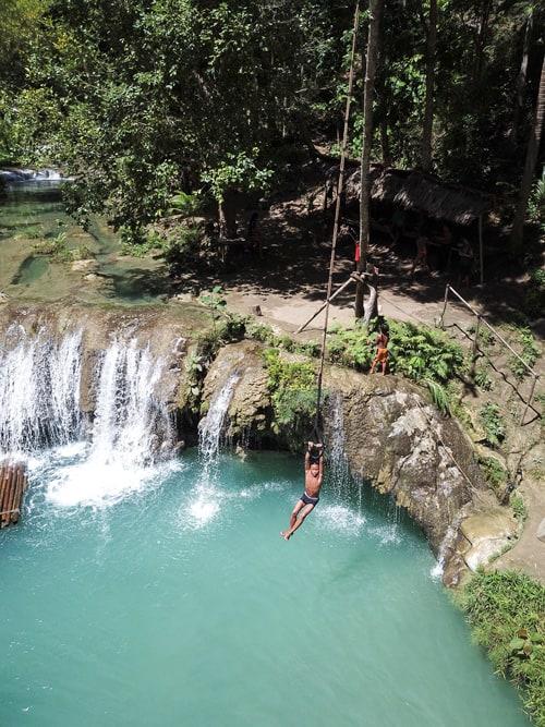 Un niño se lanza desde el columpio del tercer nivel de las Cambugahay Falls